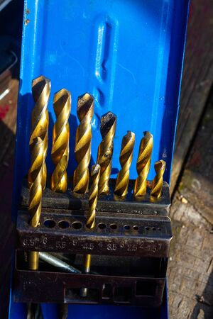 Golden incomplete set of drill bits shining in the sun