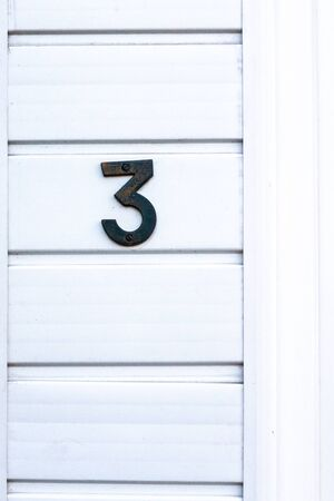 House number 3 on a white wall Stock Photo