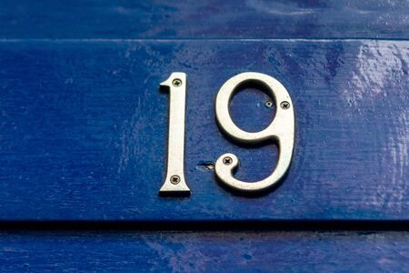 House number 19 on a blue wooden front door