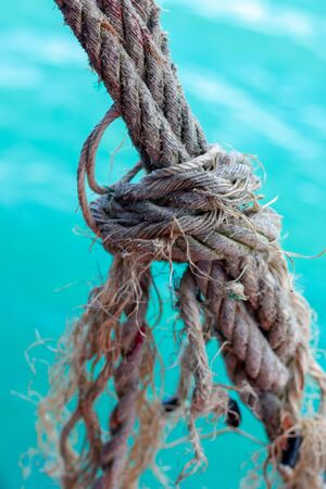 Ship's rope knotted, worn and frayed over turquoise ocean water in Thailand