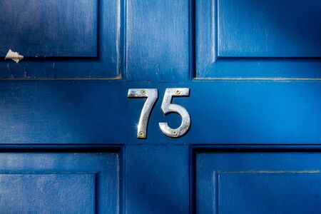 House number 75 on a blue wooden front door