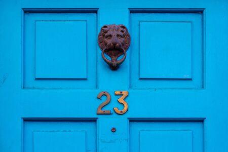 Numero civico 23 su una porta anteriore in legno blu con battente in metallo decorato metal