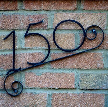 House number 150 on a brick wall
