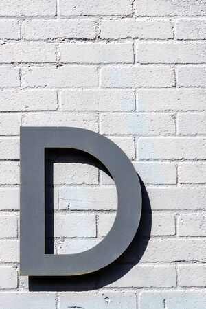The letter d in brushed steel on a brick wall with pronounced shadow