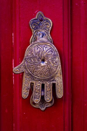 Hand of Fatima, a typical Moroccan design, as a door knocker on a red wooden front door