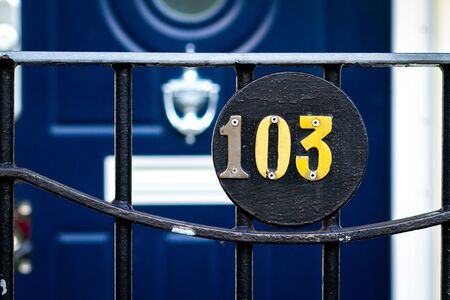 House number 103 on a round plaque in front of a blue wooden front door