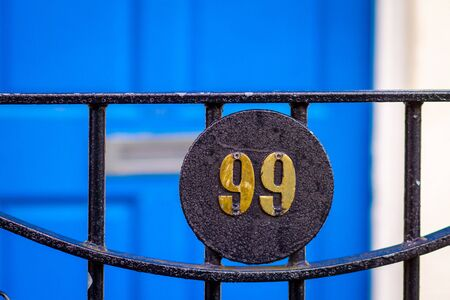House number 99 on a black iron gate in front of a blue wooden front door