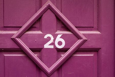 House number 26 on a purple wooden front door in a picture frame at a 45 degree angle