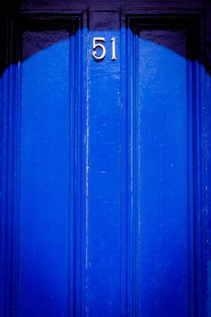 House number 51 on a royal blue wooden front door with vertical lines in London