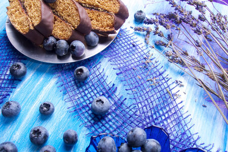 Blueberries and chocolate with lavender and spoon on wooden board photo