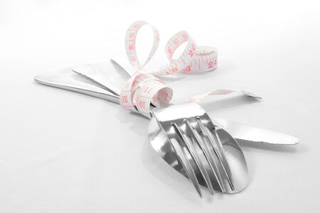 Motivation for losing weight - centimetre and spoon, fork and knife photo