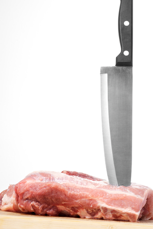 Raw red meat with knife on wooden board photo