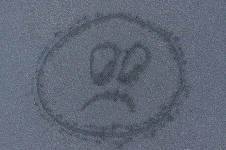 Sad smile print on the black sand beach