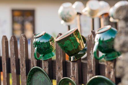DIY concept. Ceramic handmade decorative glazed dishes on fence...