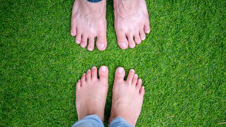 pair of bare feet heathy man and woman standing opposite on soft refreshing green grasses lawn yard with copy space.