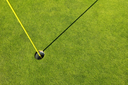 Golf hole in a green grass field background photo