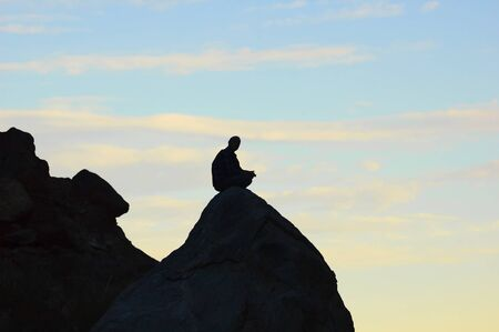 Meditating man sitting on top of a rock in the mountains  photo