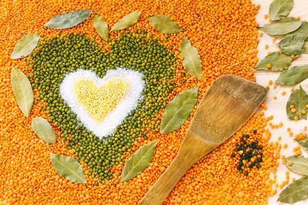 lenteja: Heart shape made of mixed yellow wheat grains, white salt, green mung beans, red  orange lentils and bay leaves on light wooden table surface with wooden spatula and black pepper, top view. Dry cooking ingredients for a healthy soup.