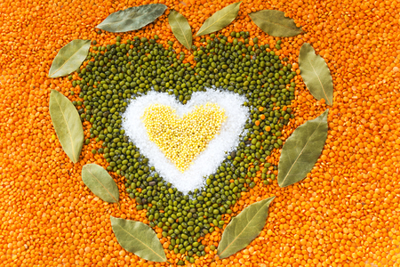 Heart shape made of mixed wheat grains, salt, green mung beans, red lentils and bay leaves on table, top view. Dry cooking ingredients for a healthy soup. Stock Photo