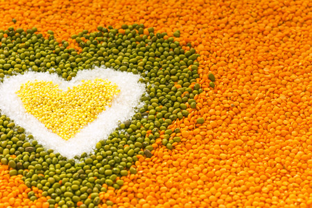 lenteja: Heart shape background made of mixed wheat grains, white salt, green mung beans, orange red lentils. Dry cooking ingredients for a healthy diet soup. Food background.