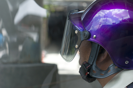 Side view of asian man wearing glossy purple helmet while riding motorbike in city Banque d'images