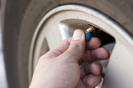Close up male hand removing blue plastic car air valve cap before tire inflation