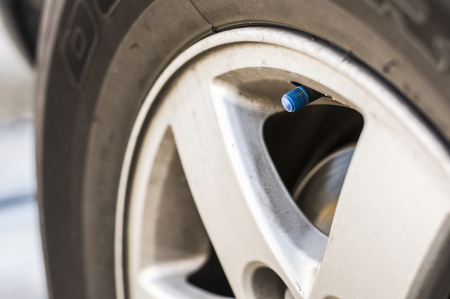 Close up blue plastic car air valve cap, position for tire inflation