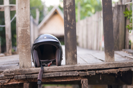 Helmet for motorbike safety in front of wooden house in rural area, law enforcement and policy for accident reduction.