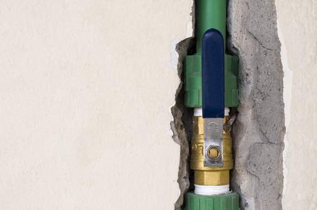 Opened brass ball valve connected to PPR pipe inside wall, clean water pipe in household and industrial Banque d'images
