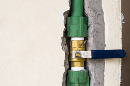Closed brass ball valve connected to PPR pipe inside wall, clean water pipe in household and industrial