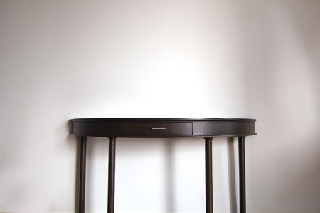 Teak wood table in front of wall with shadow Banque d'images