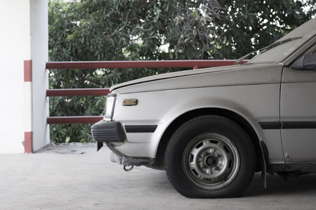 Old style scene of abandoned dusty old japanese car in car park