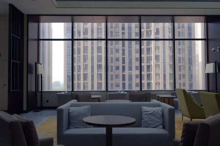 Blue couches in stylish room, high ceiling. Minimal lounge in front of glass window and high rise building view.