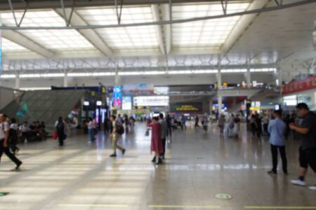 Defocused photo of people in train station hall in China, massive people who will travel. Transportation terminal interior on holiday.