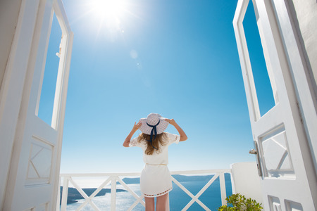 hotel balcony: Pretty woman in white dress on Santorini in Creta