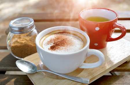 outdoor lighting: Hot cappuccino coffee on the  wooden table style in outdoor morning low and soft lighting. Stock Photo