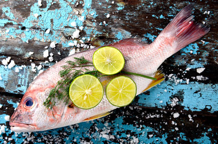 Fresh red snapper fish from fishery market with salt and lemon set on wooden plate.