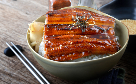 based: Japanese eel grilled with rice or Unagi don set on plate in Japanese style with studio lighting. Stock Photo