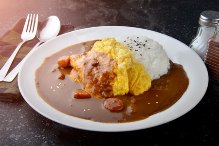 Rice with omelette curry in Japanese style or omu kare in white  plate ready to eat.
