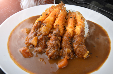 condensed: Rice with deep fried shrimp and curry in Japanese style or ebi kare in white  plate ready to eat.