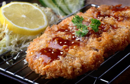 Japanese deep fried pork or tonkatsu with sauce fill on top in studio lighting. Archivio Fotografico