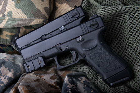 Pistal automatic short hand gun in the  US army prop background photo in lowlighting and dark shadow concept. Stock Photo