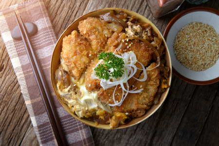 Katsudon or Japanese style fried pork roast with eeg and Japanese ingredient mixed on rice ready to serve in studio low lighting. Banco de Imagens - 84295537