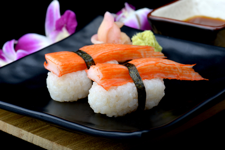 Crab stick sushi or Japanese kani sushi set on black plate with wasabi and sushi sauce with flash lighting.