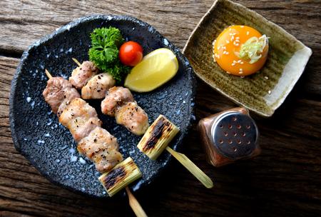Butabara yakitori o parrilla japonesa de tocino con sal y salsa sirven en el restaurante izakaya. Foto de archivo