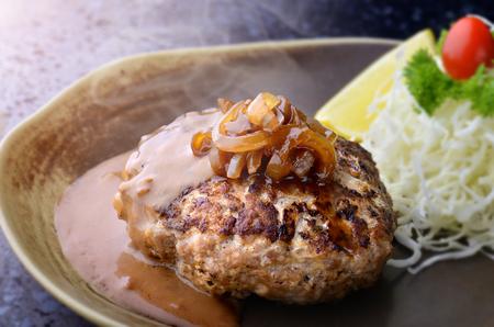 Hamburger steak in Japanese style or hambagu serve with fresh vegetable salad and set in Japanese style dish.