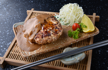 condensed: Hamburger steak in Japanese style or hambagu serve with fresh vegetable salad and set in Japanese style dish.