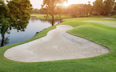 야외 골프 아침 일출 조명에 녹색 골프 페어 웨이 사진에서 모래 벙커.