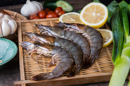 Fresh raw shrimps set with vegatables on the bamboo basket ready for cooking. Stock Photo