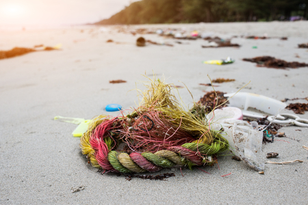 The plastic used rope be garbage on the beach photo with outdoor sunset low lighting.